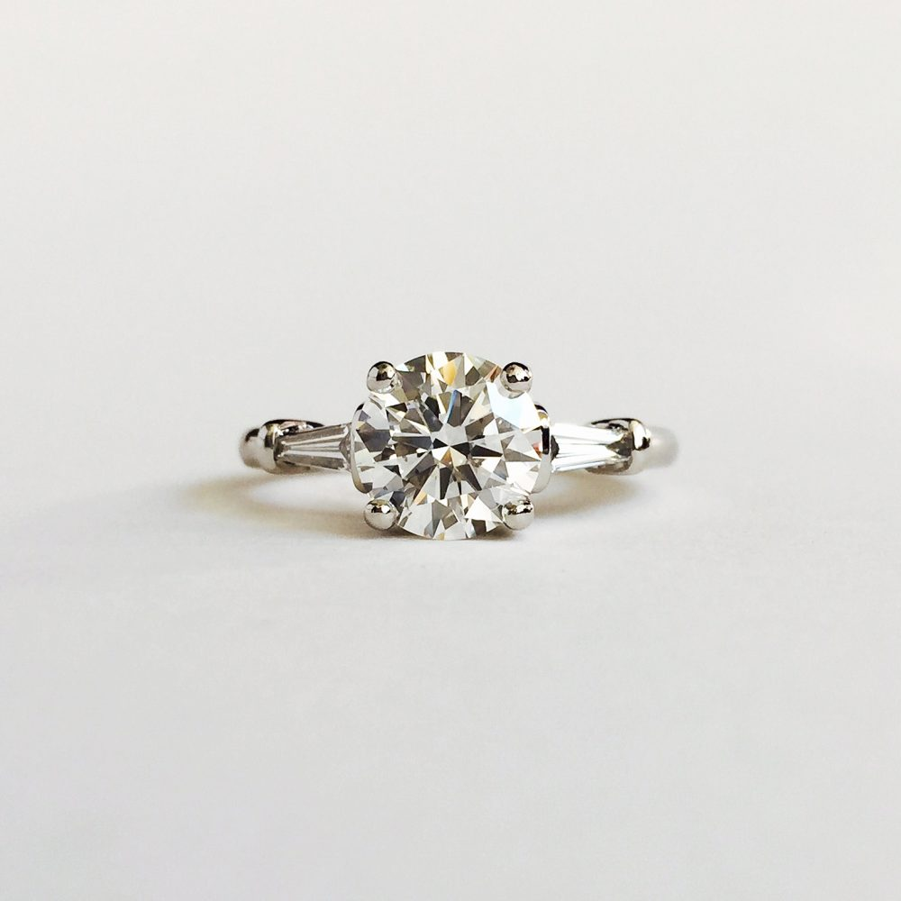 round diamond with tapered baguettes engagement ring