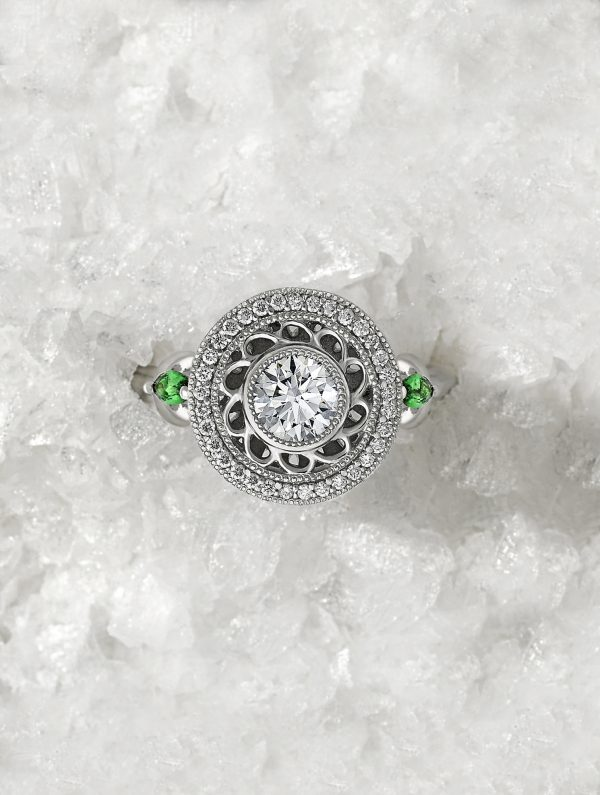 round diamond with filigree detail halo with Marquise tsavorites set in platinum