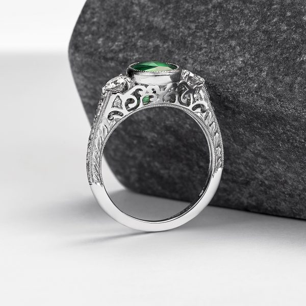 emerald engagement ring with filigree cut outs and hand engraving