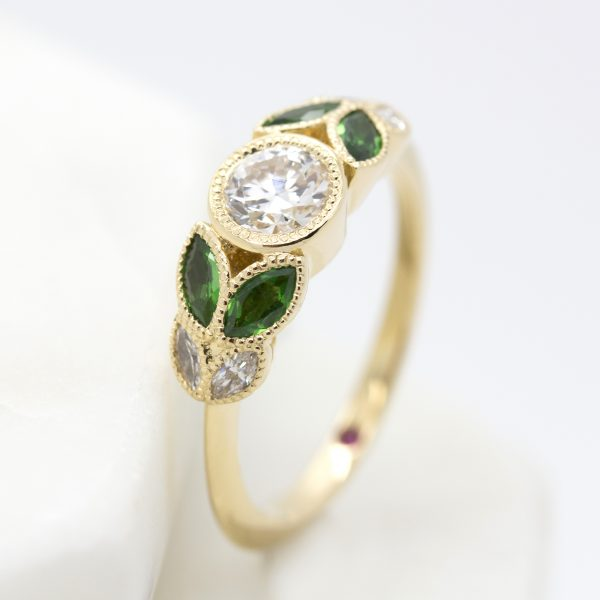 bezel set round diamond with marquise emerald and diamonds set in yellow gold organic inspired engagement ring