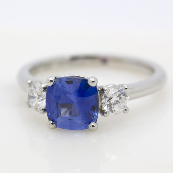 blue cushion cut sapphire trilogy engagement ring with diamonds