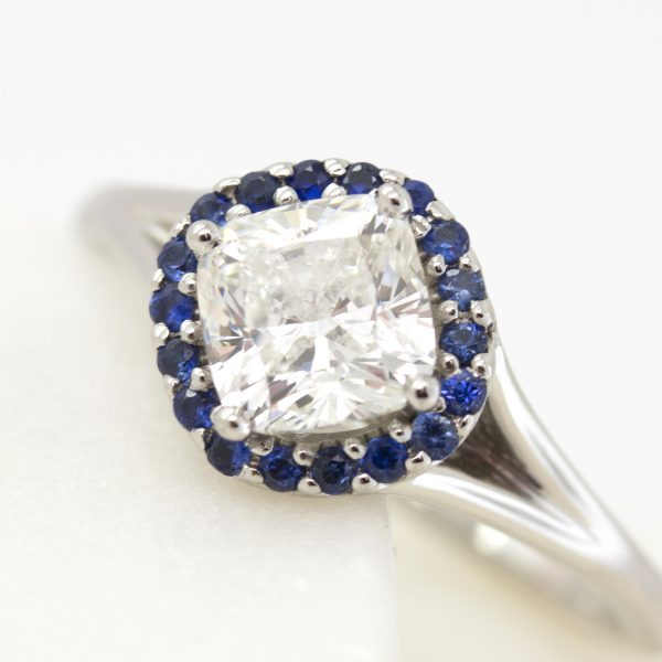 cushion cut centre diamond with blue sapphire halo set on a bias with split shank engagement ring