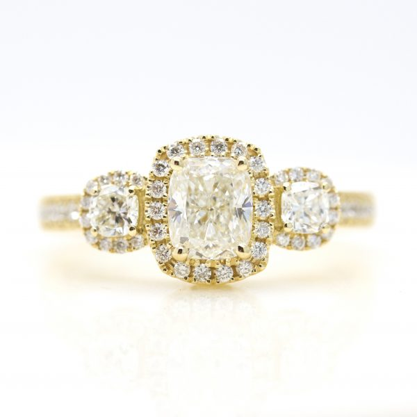 cushion cut diamond diamond halo trilogy engagement ring in yellow gold