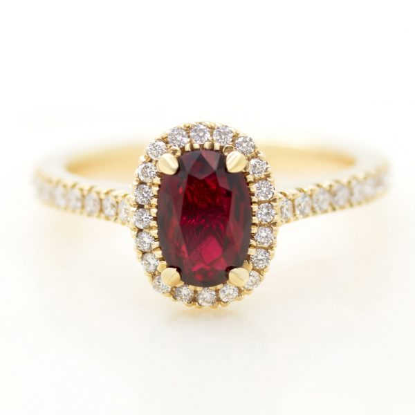 elongated oval ruby engagement ring with a yellow gold diamond halo
