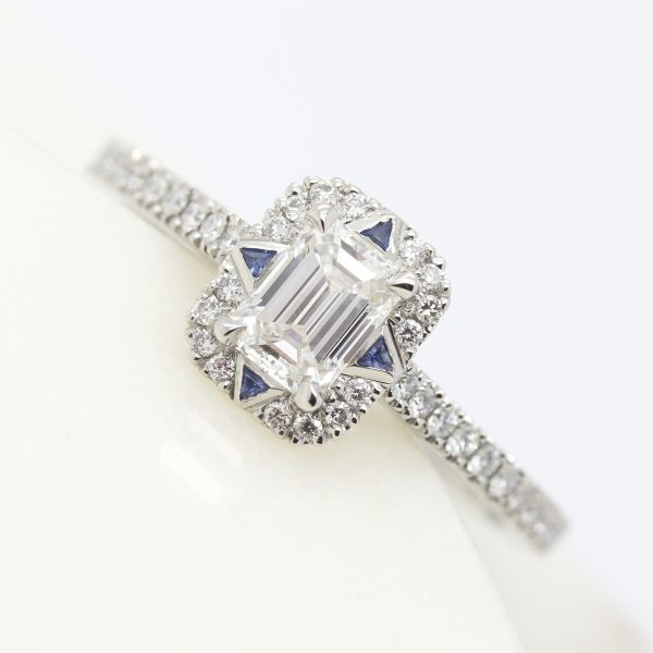 emerald cut diamond halo engagement ring with trillion blue sapphires