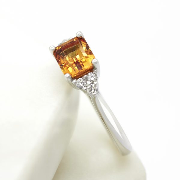 emerald cut orange sapphire with three round diamond accent stones set in platinum