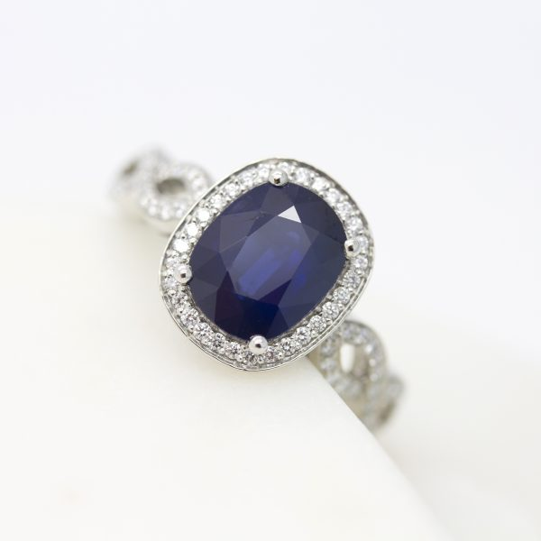 oval blue sapphire with diamond halo and twisted pave band