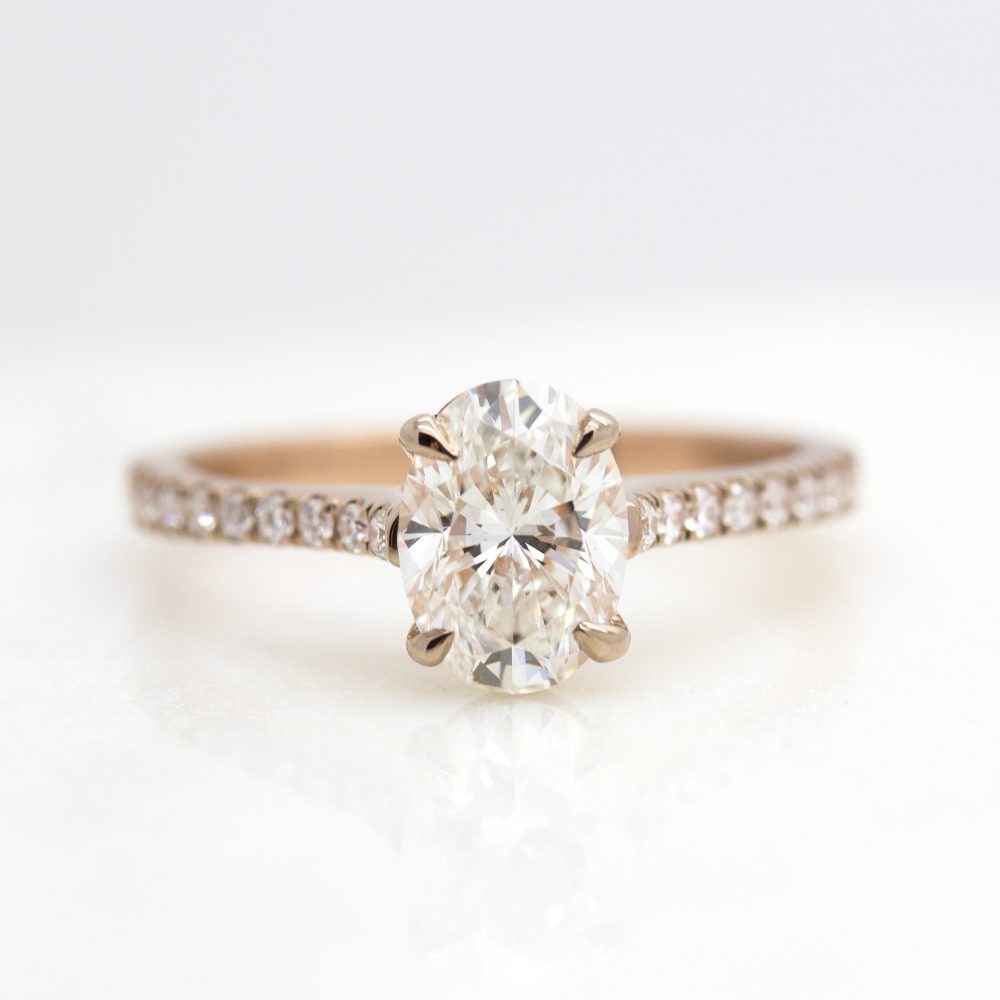oval claw set diamond with pave diamond engagement ring