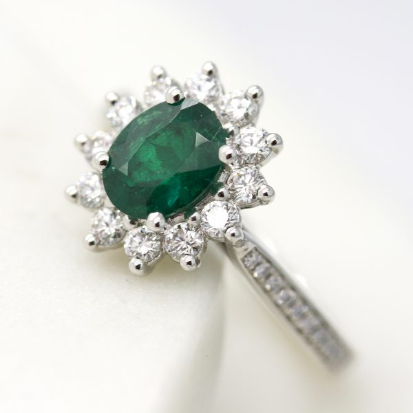 oval emerald with round diamond halo and diamond bead set engagement ring