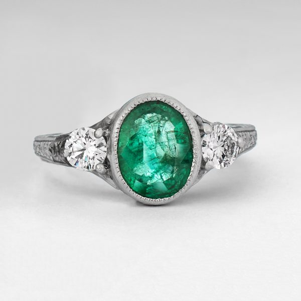 oval emerald with round side diamonds and milgrain