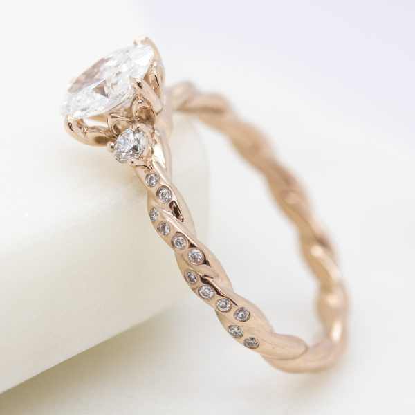 rose gold twisted engagement ring with bezel set round diamonds