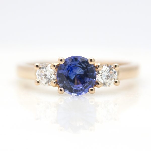 round blue sapphire trilogy engagement ring with round diamond accent stones