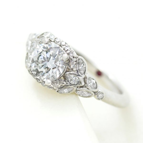 round diamond engagement ring with marquise accent stones in a leaf inspired design