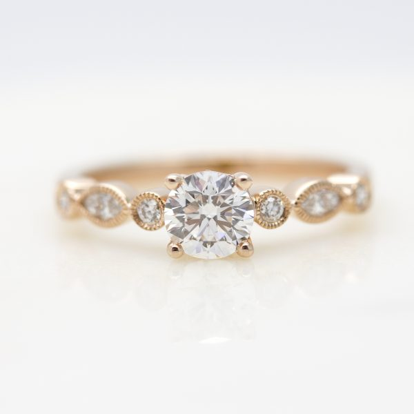round diamond with marquise and round diamonds on the band with milgrain
