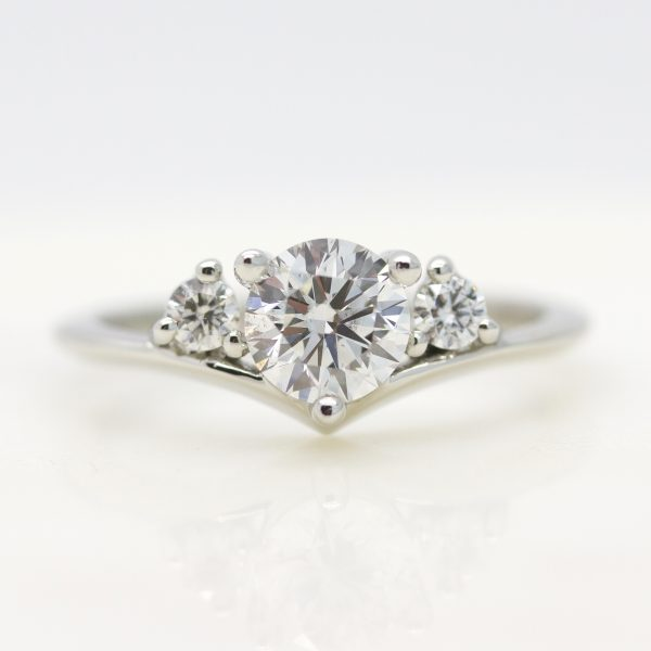 round diamond with round diamond accent stones and chevron platinum band engagement ring