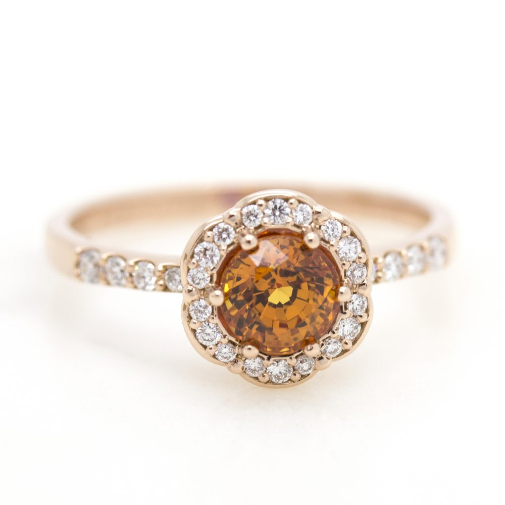 round orange sapphire with diamond halo set in rose gold