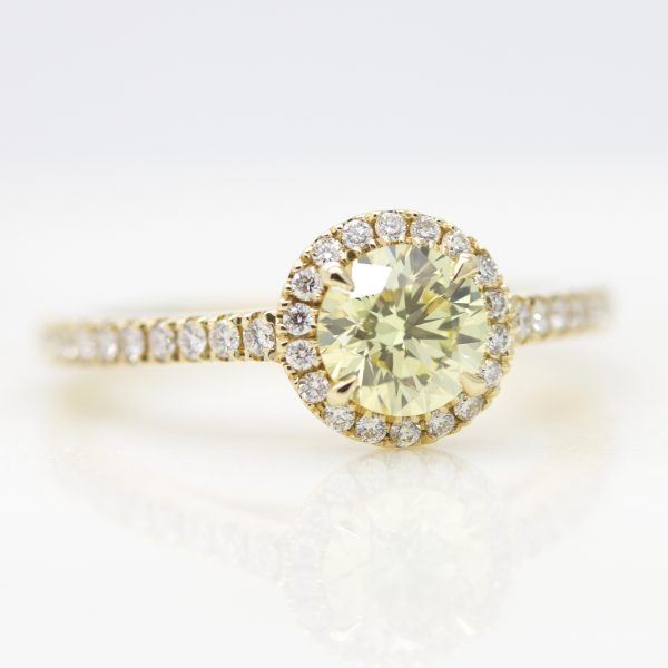 round yellow diamond with white diamond halo set in yellow gold engagement ring