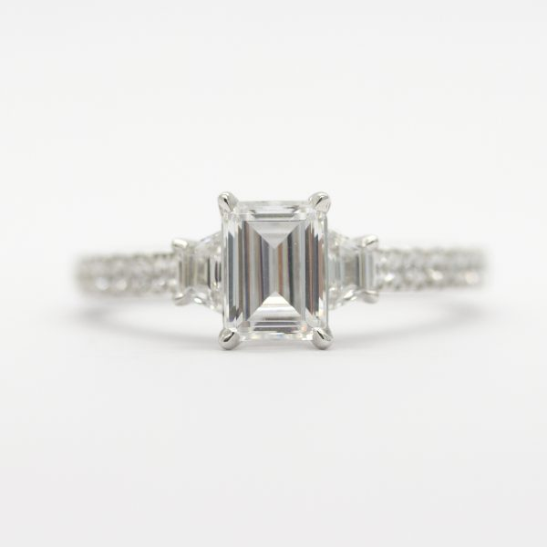 Emerald cut diamond with trapezoid diamond side stones