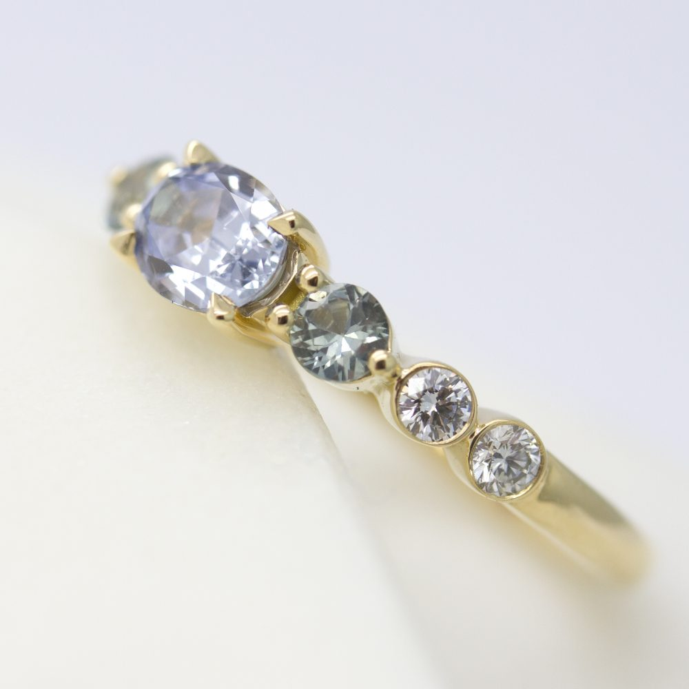 blue sapphire engagement ring with bezel set round diamonds set in yellow gold
