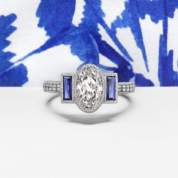 oval diamond with blue sapphire baguettes hand engraving and milgrain