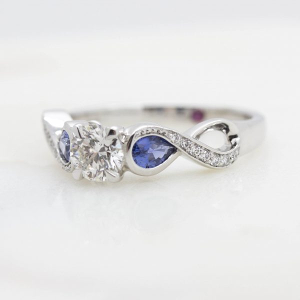 round centre diamond with side pear bezel set blue sapphire in an infinity symbol engagement ring