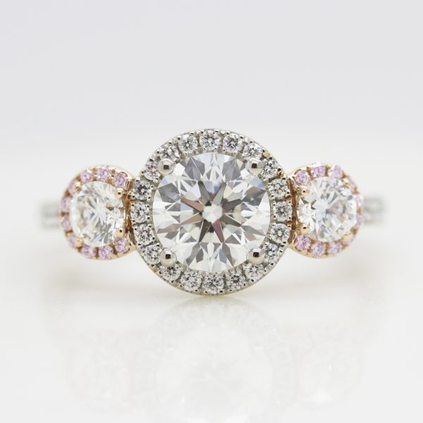 round diamond trilogy engagement ring with mixed metal and pink sapphire and diamond halo