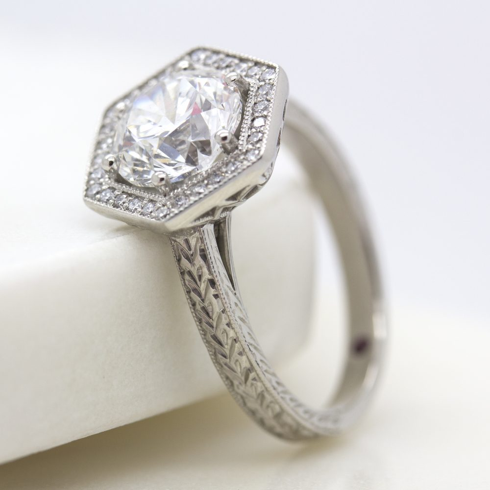 round diamond with hexagonal diamond halo and hand engraved band