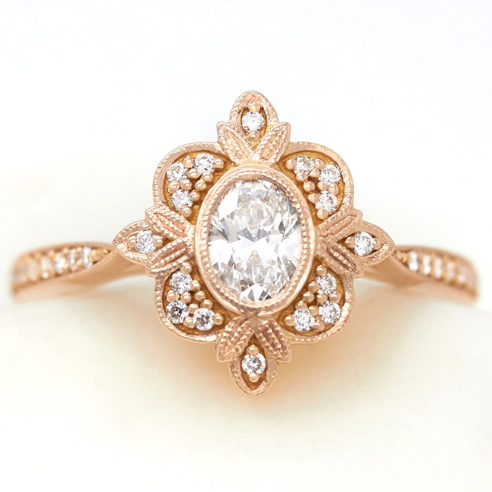 vintage oval diamond rose gold engagement ring with accent diamonds and milgrain detail