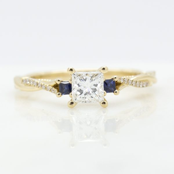 princess cut diamond trilogy engagement ring with two blue sapphires and pave twisted band