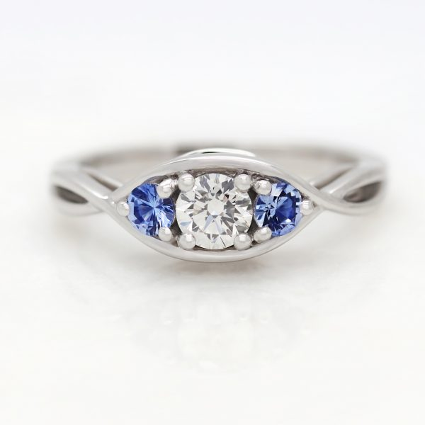 round diamond and blue sapphire trilogy engagement ring with sweeping infinity band