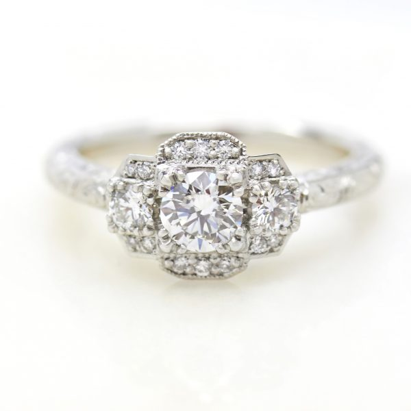 round diamond trilogy engagement ring with bead set milgrain and hand engraving