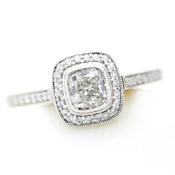 cushion cut diamond halo engagement ring with milgrain and bezel setting in platinum