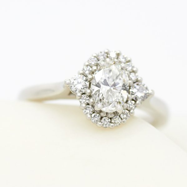 oval diamond with accent round diamond halo engagement ring