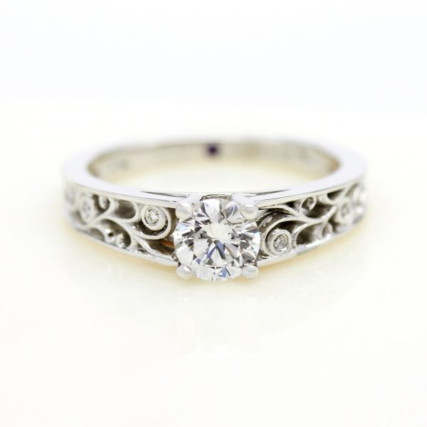 round diamond engagement ring with cutout filigree details