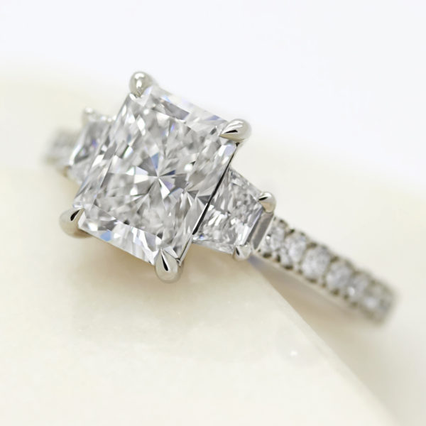 radiant cut diamond with trillion diamond side accent stones engagement ring