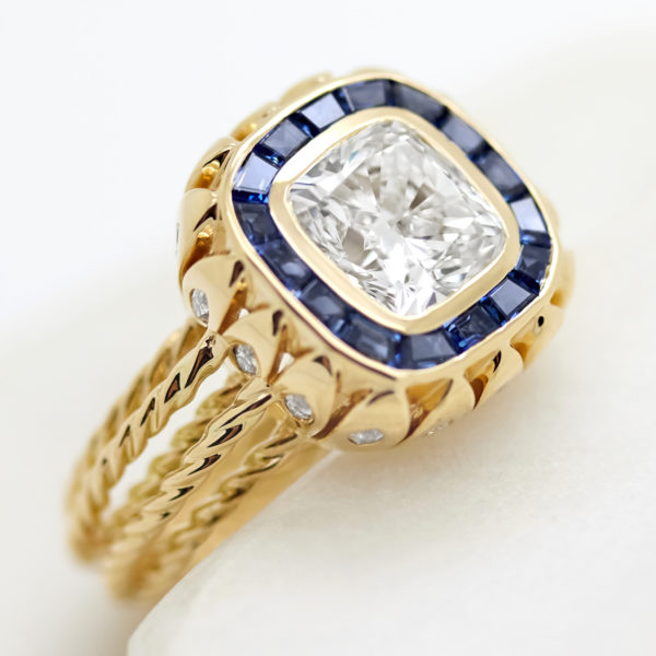 cushion cut diamond with custom cut blue sapphire halo and rope band in yellow gold