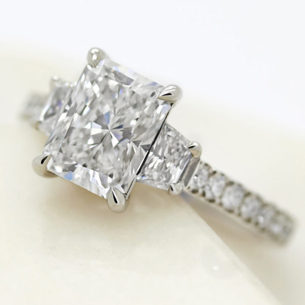 radiant cut diamond with diamond trapezoid side stones engagement ring