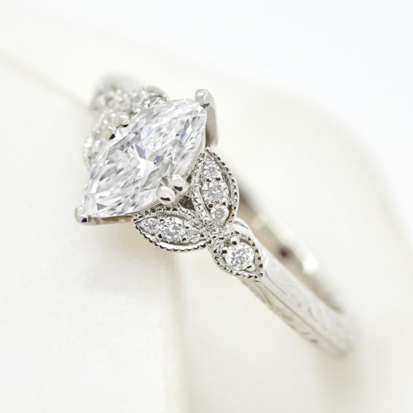custom marquise diamond engagement ring with floral inspired accent stones