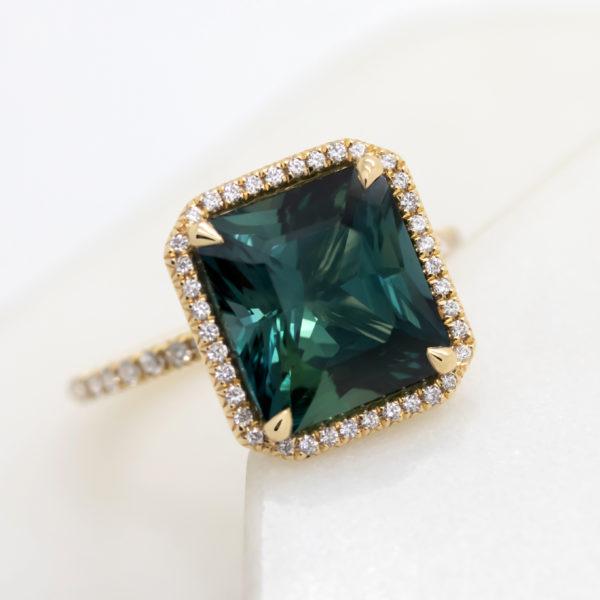 square dark teal sapphire pave diamond halo yellow gold