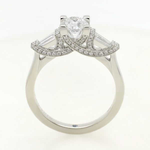 Round diamond trilogy engagement ring with tapered baguette diamonds and bead set pave under collet sweeping detail