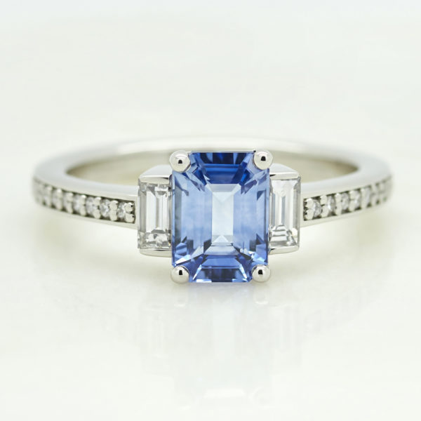 emerald cut blue sapphire with diamond baguette side stones trilogy engagement ring