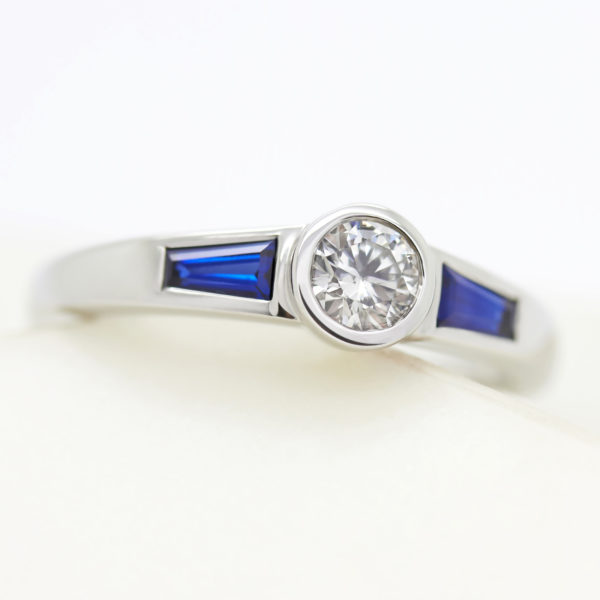 round diamond trilogy engagement ring with tapered blue sapphire sides