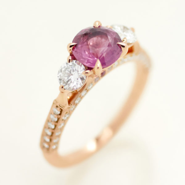 round pink sapphire trilogy engagement ring with round diamond accent stones and pave set in rose gold