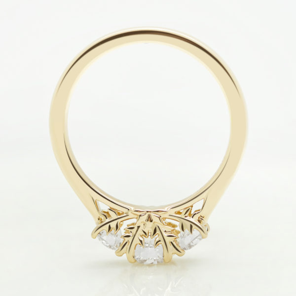 yellow gold trilogy engagement ring with organic engraved leaf detail